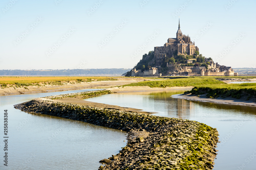 Fototapeta View of the Mont Saint-Michel tidal island, located in France on the limit between Normandy and Brittany, at high tide with a stone dyke on the Couesnon river in the foreground.