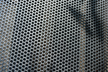 Metal mesh, background, with round identical holes, metal structure with shadow and light