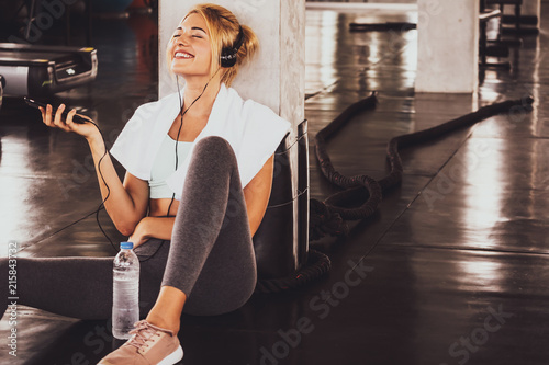Foto  Young happy woman sitting and listening to music by smartphone while having exercise break at the gym