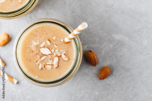 Photo Stands Milkshake Banana almond smoothie with cinnamon and oat flakes and coconut milk in glass jars