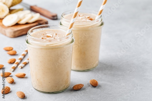 Tuinposter Milkshake Banana almond smoothie with cinnamon and oat flakes and coconut milk in glass jars