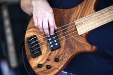 A Closeup Of A Man Playing A 5 String Bass Guitar.