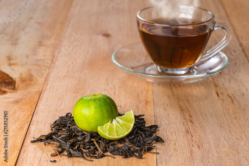 Staande foto Thee close-up lime on pile of tea on wooden table, hot drink with steam background