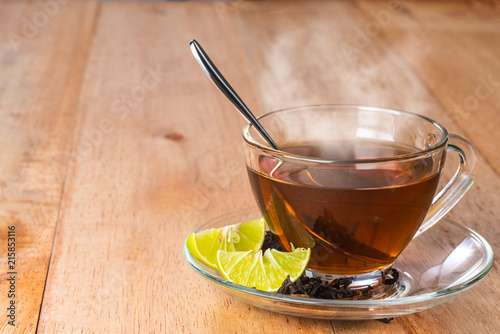 Staande foto Thee a cup of lime tea on wooden table, hot drink with steam