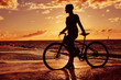 Silhouette of a girl with a bicycle on a sea coast on a sunset background.