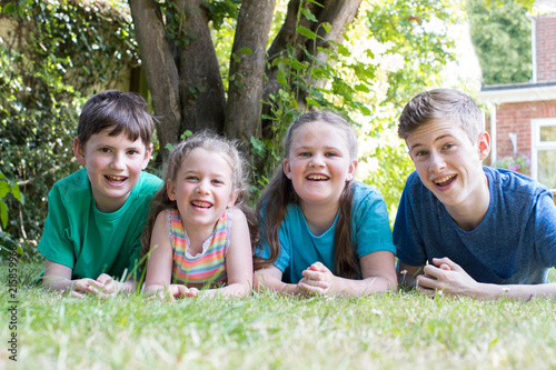 Fototapeta Portrait Of Four Brothers And Sisters Lying In Garden At Home