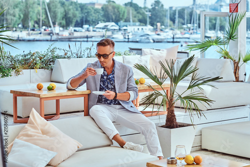 Fototapeta Fashionable successful man with stylish hair dressed in modern elegant clothes holds a cup of coffee while sitting on a sofa at outdoor cafe against the background of the city wharf. obraz