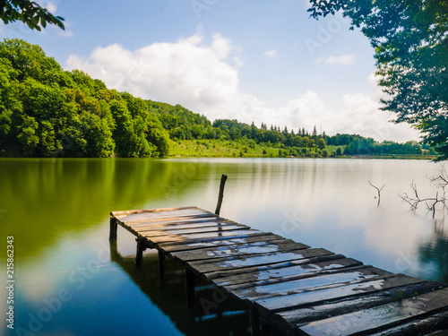 Wooden pier or jetty and a boat on lake sunset and sky reflection water.