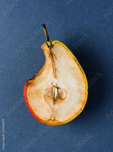 Stale old pear. Bite mark. Dark background