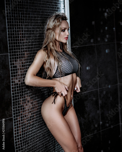 Tuinposter Akt Beautiful sexy blonde girl with wet hair. Posing in a swimsuit in the shower under the drops of water