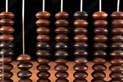 Photo antique abacus with knuckles on a table on a black background
