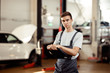 A young and qualified automechanic is standing near cars while filling in a form