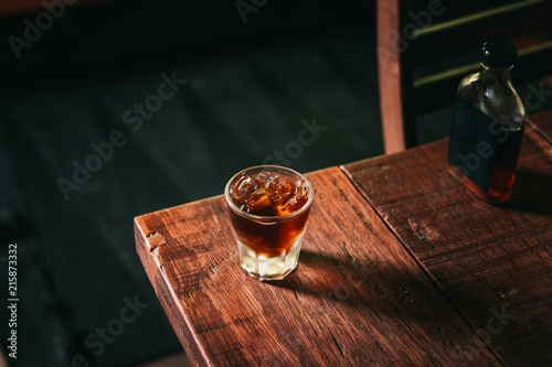 Photo Cold brew coffee with ice cubes and the glass bottle on the wooden table from above