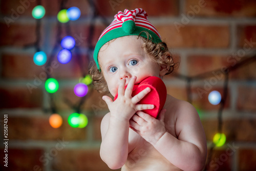 d8cbbc12a7009 Beautiful little baby boy in elf hat with gift box and fairy lights on  background.