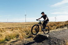 A Man In A Black T-shirt Lifting The Front Of His Bike Over A Rock On A Trail Surrounded By Wind Turbines In Scotland