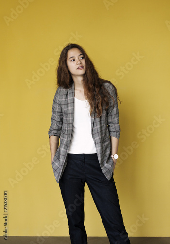 Portrait of confident young woman against a yellow wall.