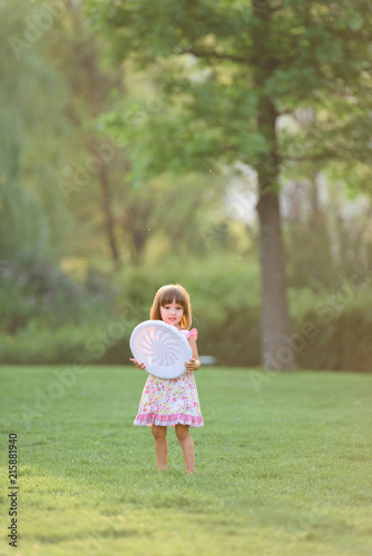 Sweet girl holding a frisbee toy outdoor in nature