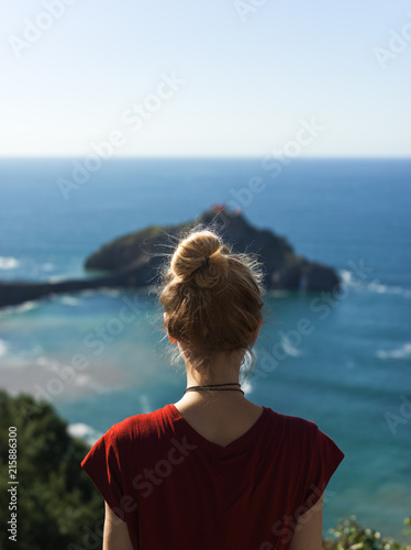 Woman standing on cliff at sea