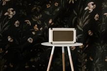 Vintage White Music Speaker On Modern White Table In Front Of Vintage Floral Background