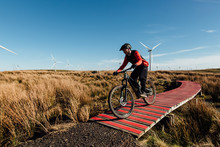 A Man In A Red And Black Jersey Cycling At Speed Along A Red Wooden Track At A Bike Park On A Wind Farm In Scotland