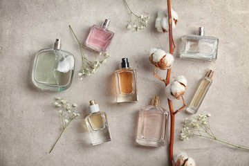 Beautiful composition with bottles of perfume on light background, flat lay