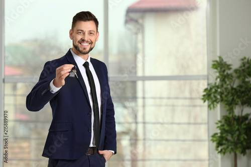 Real estate agent holding house key, indoors Canvas Print