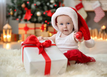Cute Baby In Santa Hat Playing With Jingle Bell At Home. Christmas Celebration