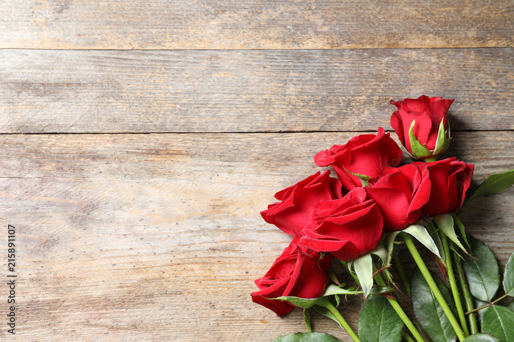 Beautiful red rose flowers on wooden background, top view
