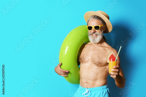 mata magnetyczna Shirtless man with inflatable ring and glass of cocktail on color background