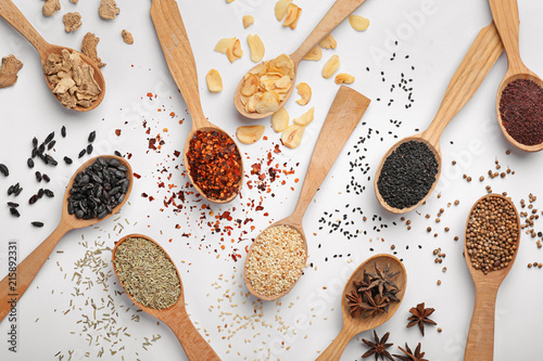 In de dag Kruiden Composition with different aromatic spices in wooden spoons on white background