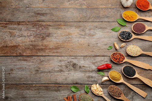 Canvas Prints Spices Flat lay composition with different aromatic spices in spoons on wooden background