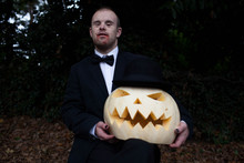 Man With Down's Syndrome Proudly Displays His Vampire Costume And Carved Pumpkin Wearing A Hat.