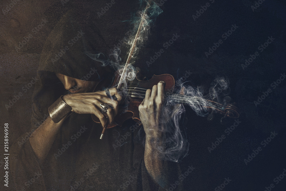 Fototapeta Dark phantom violin player, man performing a concert shrouded in smoke and fog