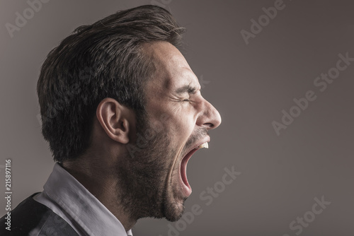 Slika na platnu Furious angry young business man shouting and yelling, side view and closeup