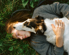 Woman Embracing With Dog On Grass
