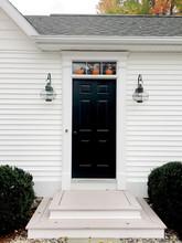 Three Tiny Pumpkins Decorate A Front Door.