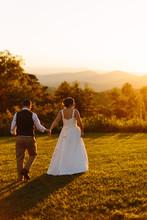 Bride And Groom Walking In Sunset Glow In North Carolina