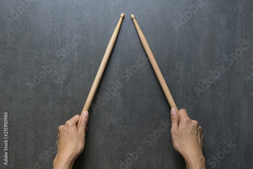 Obraz na płótnie hand holding drum stick on black table background, music practice concept