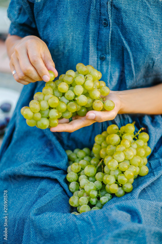 Unrecognizable woman eating green grapes