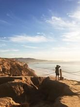Photographer On Oceanside Cliffs At Sunset