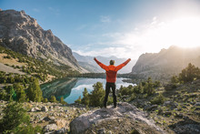 Hiker In Red Jacket Raise His Hands At A Beautiful Mountain Lake At Sunrise