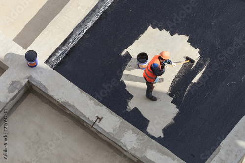 Fototapeta The worker in overalls applies an insulation coating on the concrete surface. View from above. obraz