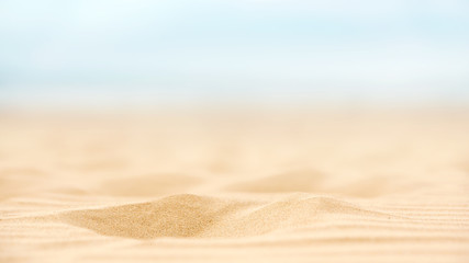 Close up sand beach with blurred sea sky background, summer day, copy space.