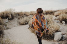 Back Side Of Boho Woman In The Desert Nature.  Artistic Photo Of Young Hipster Traveler Girl In Gypsy Look And Windy Hair, In Coachella Valley In A Desert Valley In Southern California.