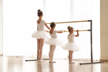 In A Dance School, A Group Of Girls And Girls Train Together At The Bar. All The Little Girls Are Dressed In White With Gathered Hair. Concept Of: Elegance, Education, Dance, Learning