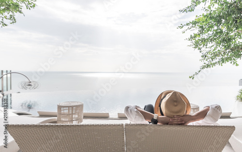 Relaxation holiday vacation of businessman take it easy resting on beach chair at swimming pool poolside beachfront resort hotel with sea or ocean view and summer sunny sky - 215938301