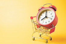 Buy Time, Shopping Cart With Red Vintage Alarm Clock Show 8 O'clock Over Yellow Background