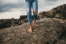 Crop Barefoot Woman In Jeans Walking On Rock