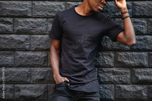 Man in blank black t-shirt standing against brick wall, cropped shot