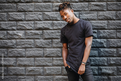 Fotografia  Handsome african american man in blank black t-shirt standing against brick wall